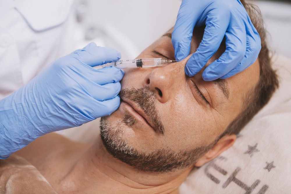 Doctor applying nose injectables to male patient's nose